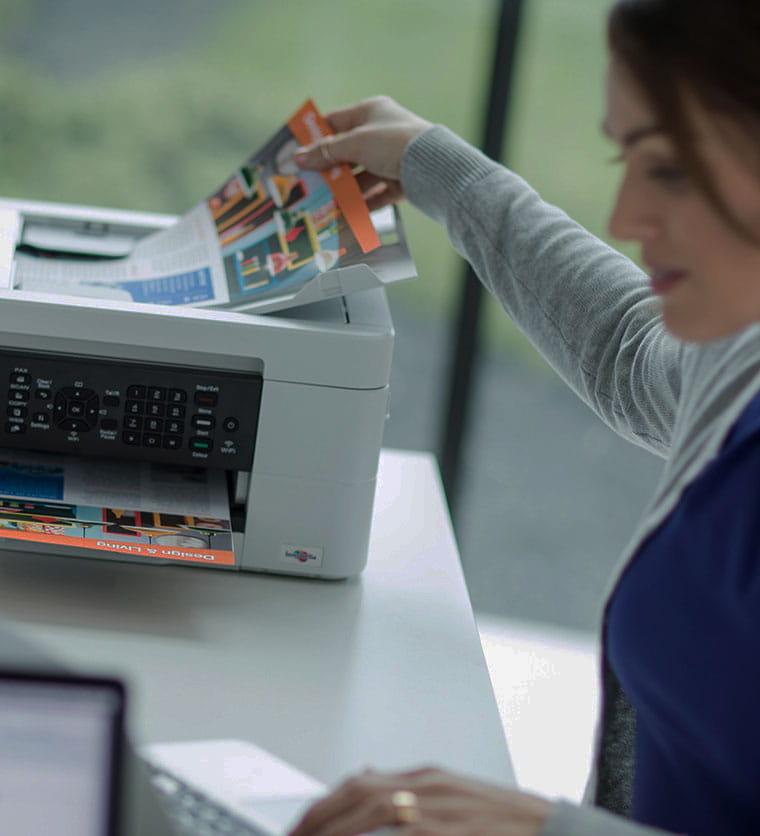 Donna che prende un foglio stampato con stampante Brother