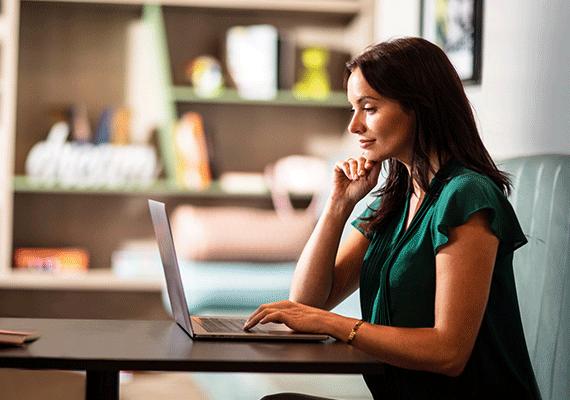 Donna lavora al computer portatile in ambiente domestico