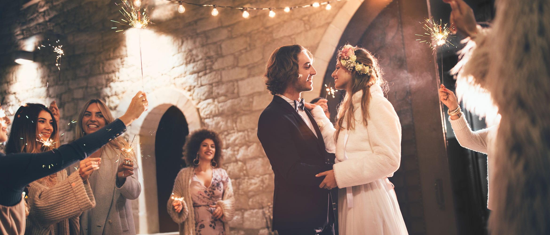 Coppia di sposi balla circondata da ospiti con bastoncini scintillanti