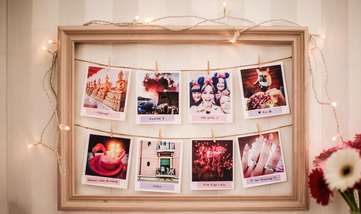Quadro con foto in formato polaroid etichettate e appese a un filo
