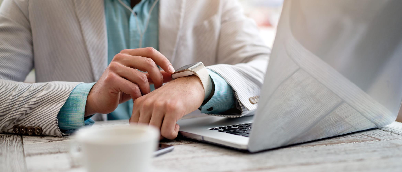 persona alla scrivania controlla email dallo smart watch