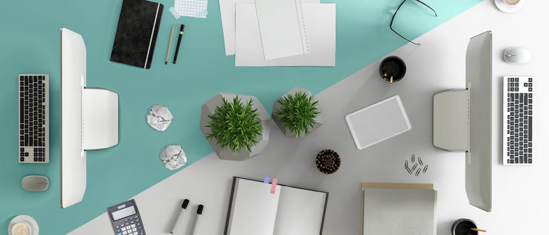 Scrivania di un ufficio con monitor pc, tastiere, agende e penne