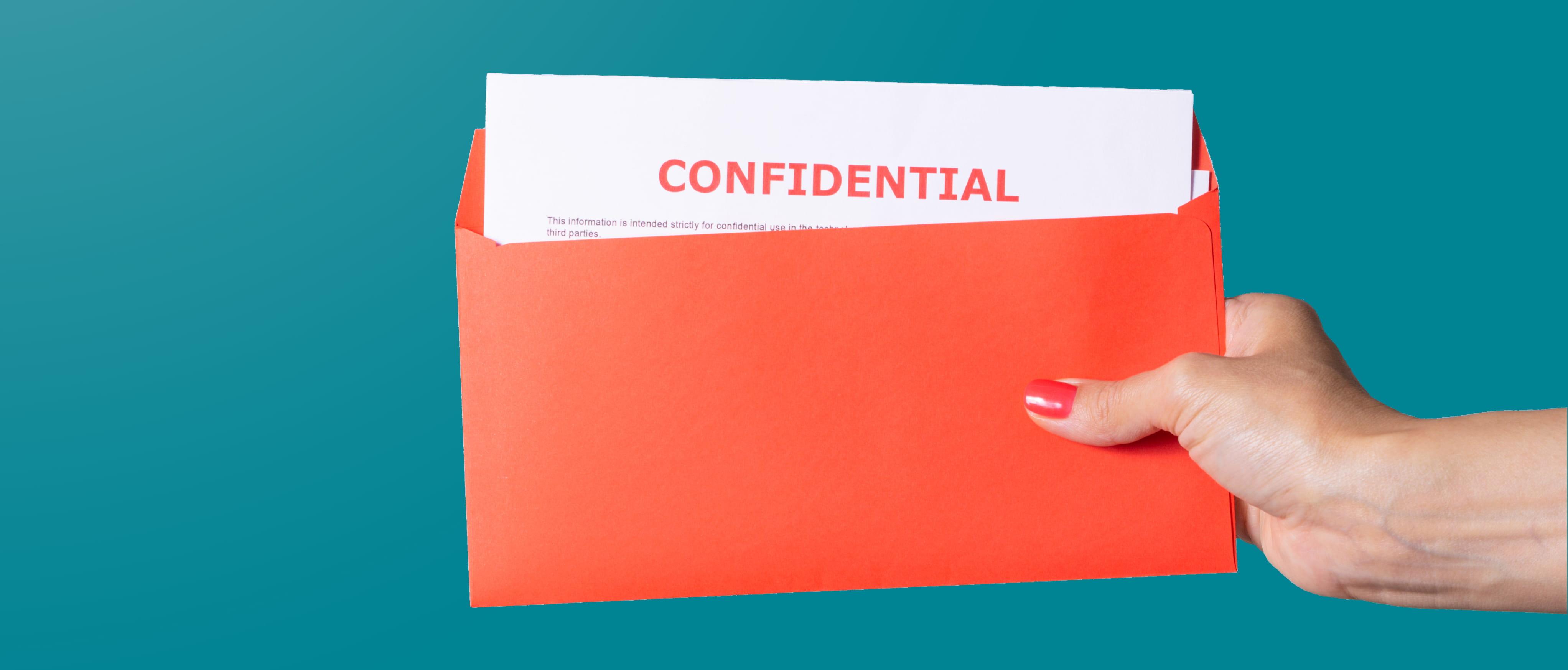 Mano di donna con busta arancione scritta confidential