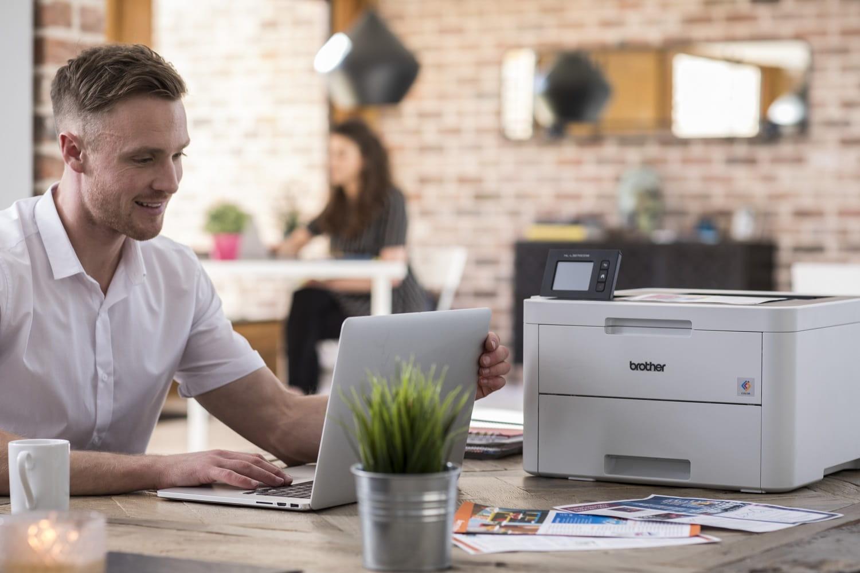Giovane lavoratore scrive al PC portatile con a fianco una stampante laser Brother