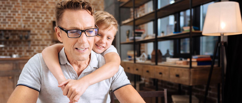 Bambino abbraccia il papà mentre sta lavorando da casa