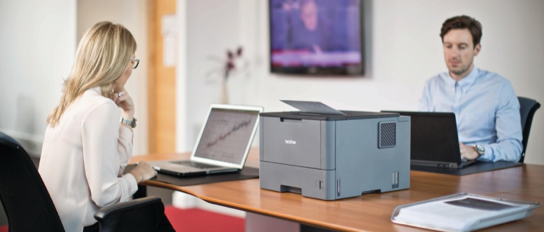 coworking tra due colleghi con stampante laser brother su scrivania in legno