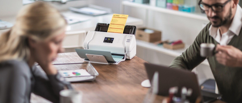 Scanner desktop Brother wireless ADS2700W in scansione su una scrivania in ufficio