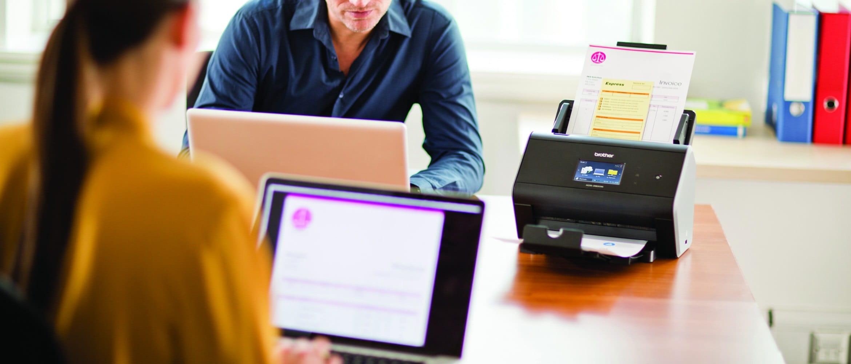 Scanner desktop Brother ADS2800W in azione in ufficio con documenti scansionati a PC tramite WiFi