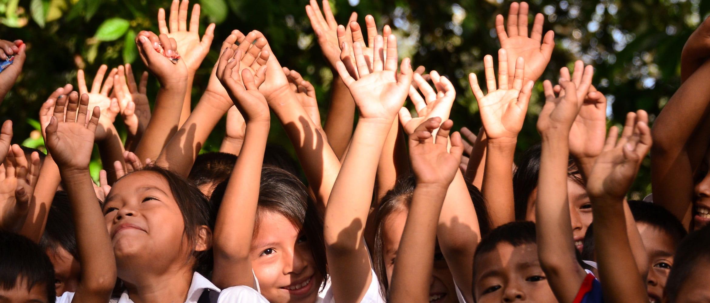 Bambini felici che alzano le mani