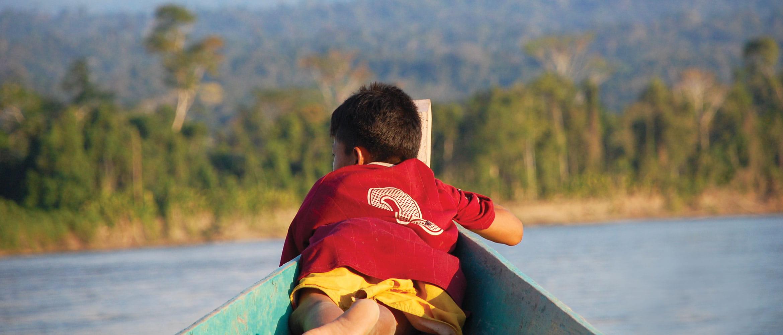 Bambino con maglietta da calcio rossa su una canoa nella foresta pluviale