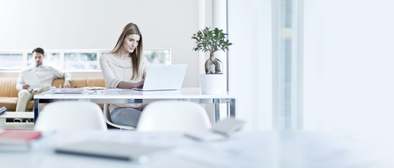 Ragazza al lavoro al PC mentre un ragazzo è seduto sul divano