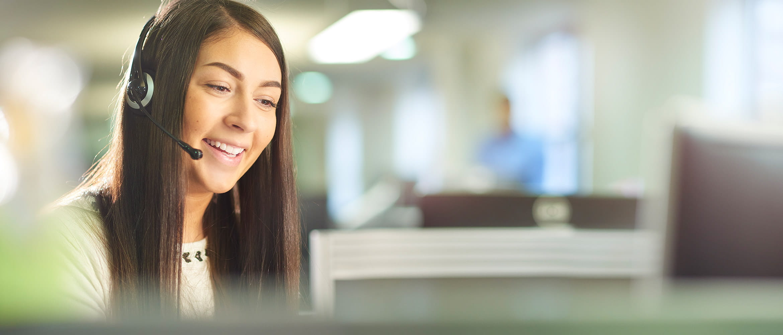 ragazza sorride con cuffie in ufficio per supporto