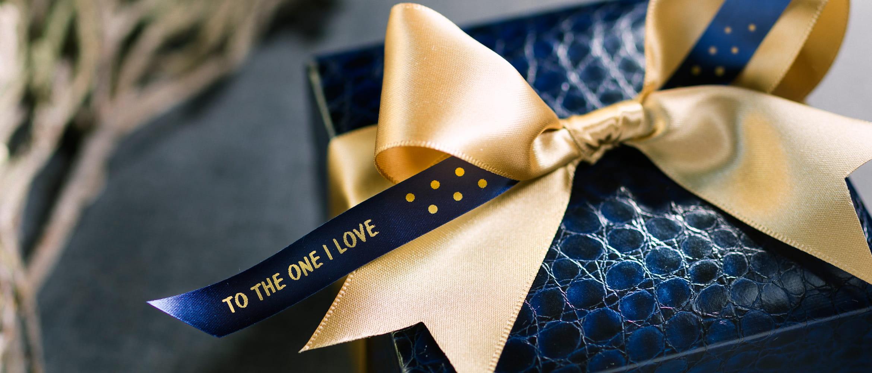 scatola regalo blu con fiocco oro e nastro Brother in tessuto oro su sfondo blu