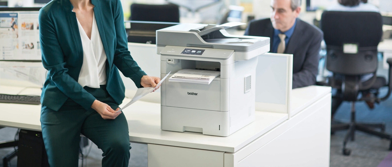 Impiegata in ufficio con foglio stampato da stampante multifunzione laser Brother DCPL6600DW