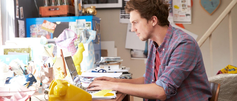 Ragazzo al lavoro al pc portatile nella sua stanza in casa