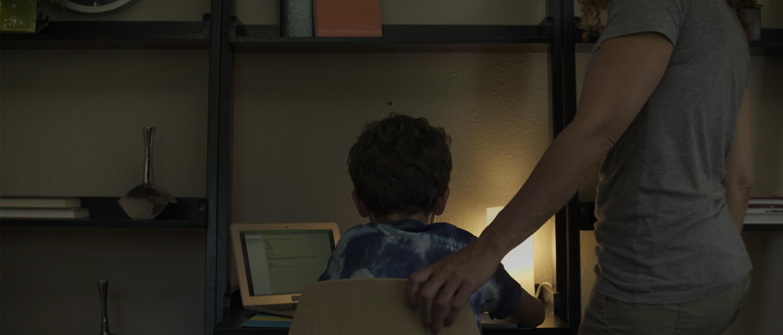 Madre che aiuta il figlio a fare i compiti seduto alla scrivania