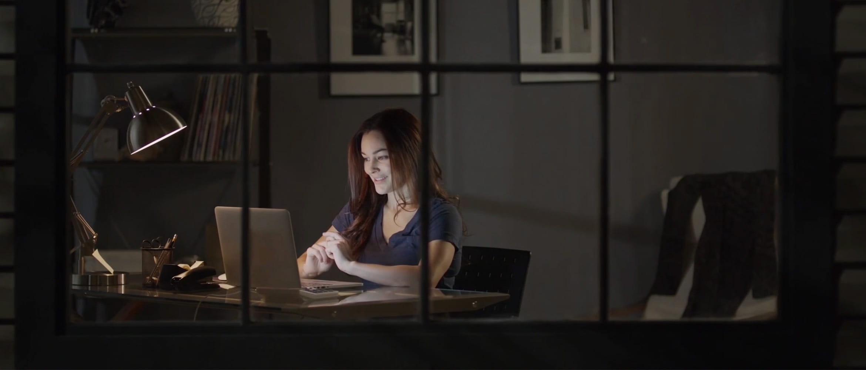 Donna seduta alla scrivania con un pc portatile in casa di sera