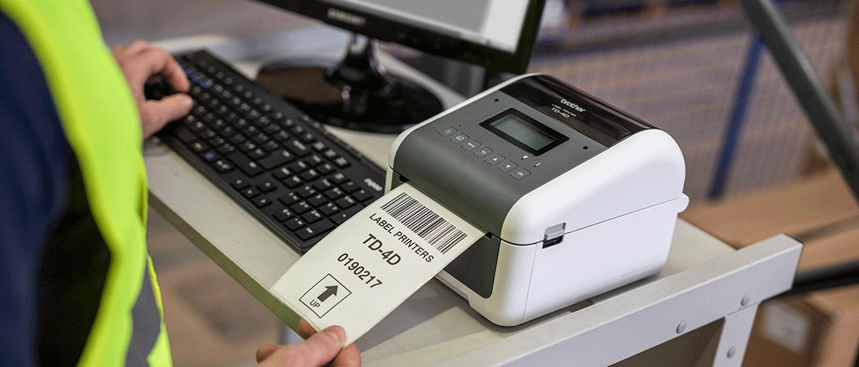 Uomo prende l'etichetta dalla stampante per etichette Brother TD-4D