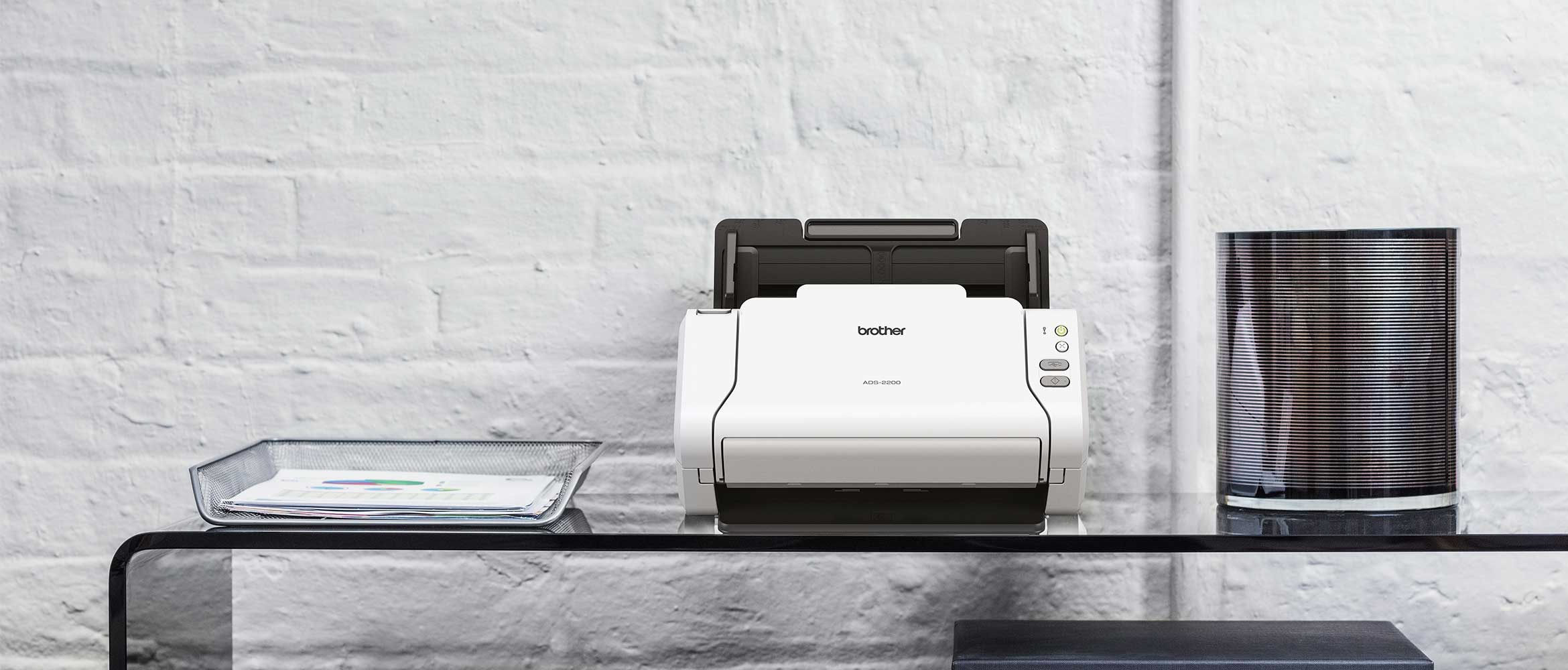 scanner desktop Brother ADS-2200 su tavolo di vetro con bordo curvo