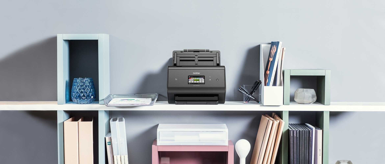 Scanner desktop Brother ADS-3600W su scaffale con libri e raccoglitori