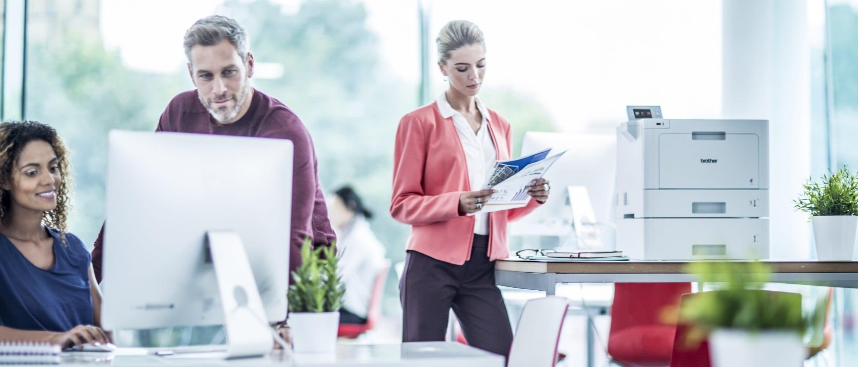 Impiegata in ufficio con foglio stampato con la stampante laser a colori professionale Brother HLL9310CDW