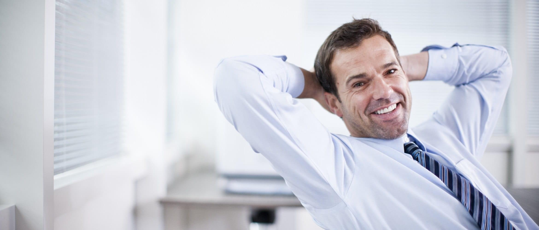 Impiegato sorridente in ufficio con camicia e cravatta