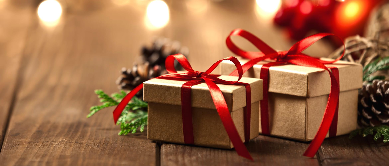 due pacchetti regalo con nastro rosso sullo sfondo candele rosse