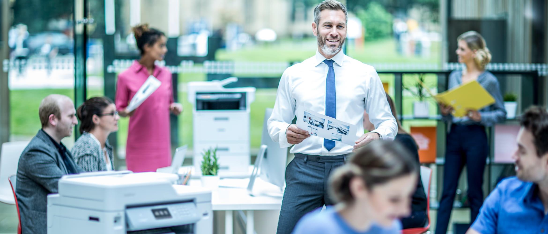colleghi in ufficio con stampanti laser monocromatiche e a colori Brother per prestazioni elevate