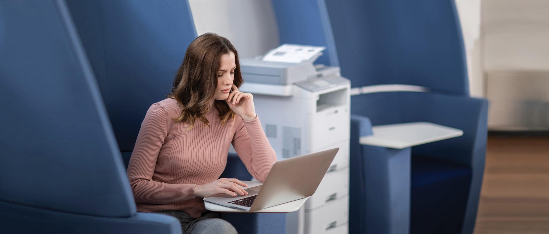 Donna seduta accanto al multifunzione Brother MFC-L6900DW in ufficio