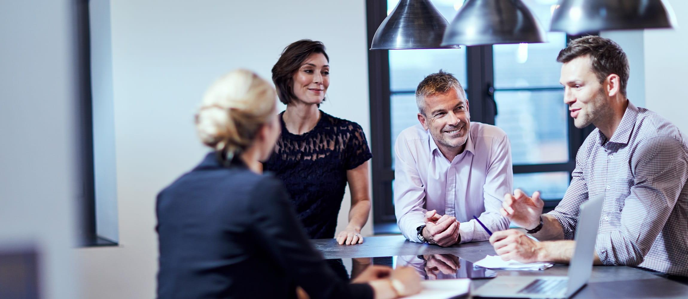 Meeting a lavoro tra due ragazze e due ragazzi sorridenti