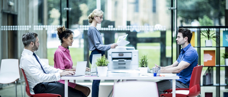 Ragazza biondo con i mano fogli stampati dalla stampante multifunzione inkjet Brother MFCJ5930DW all'interno di un ufficio