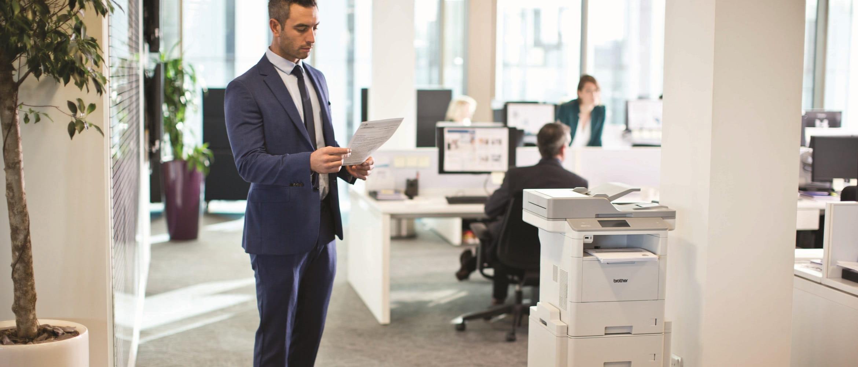 Impiegato in ufficio con foglio stampato da stampante multifunzione laser professionale Brother MFCL6900DW