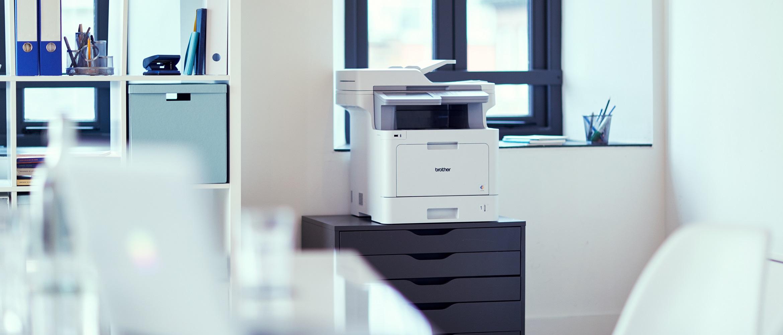Stampante multifunzione laser a colori Brother in ufficio su un mobiletto per documenti