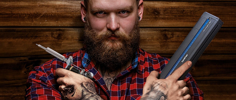 Uomo con barba e camicia a quadri con in mano Brother Stencil Machine e ago per tatuaggi