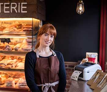 Donna in una caffetteria con stampante di etichette TD sul bancone