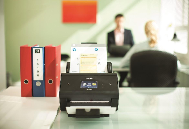 Scanner desktop Brother ADS-3600W in scansione su scrivania d'ufficio
