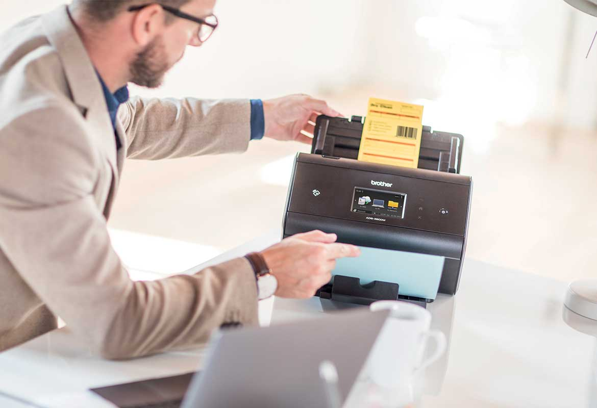 Man sat at desk wearing glasses scanning a document with barcode on a scanner