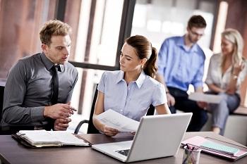 Colleghi che dialogano alla scrivania davanti ad un pc portatile