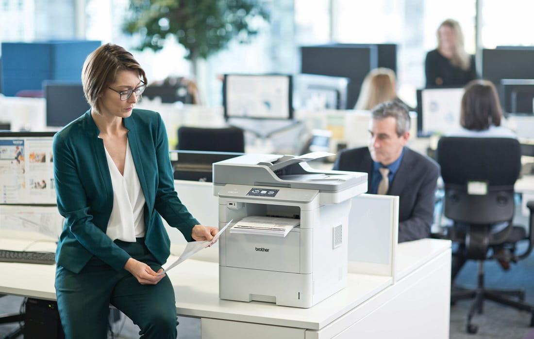 Stampante multifunzione laser mono Brother DCP-L6600DW appoggiata su scrivania in ufficio