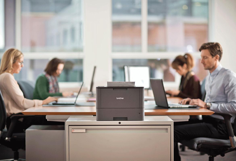Stampante laser Brother su un mobile con persone sedute alla scrivania