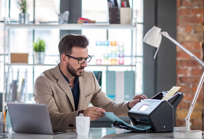 Uomo alla scrivania scansiona documento con Scanner Brother e laptop