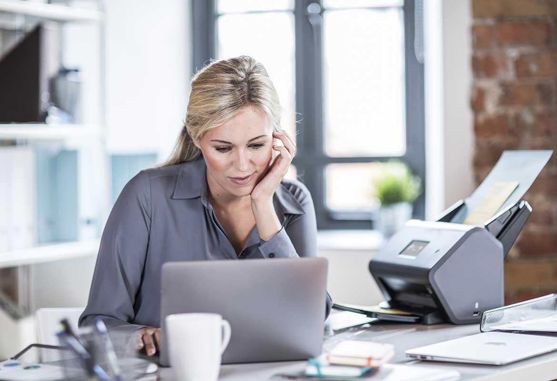 Donna seduta alla scrivania con laptop e scanner Brother ADS-3600W