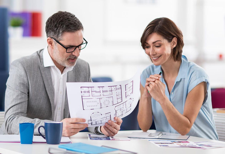 Uomo e donna seduti alla scrivania guardano un documento in A3