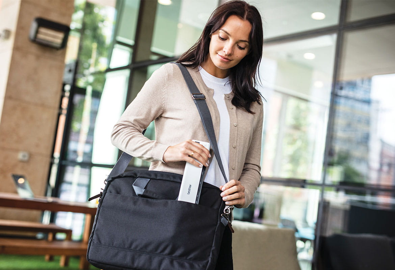 Donna mentre cammina mette lo scanner nella borsa del laptop