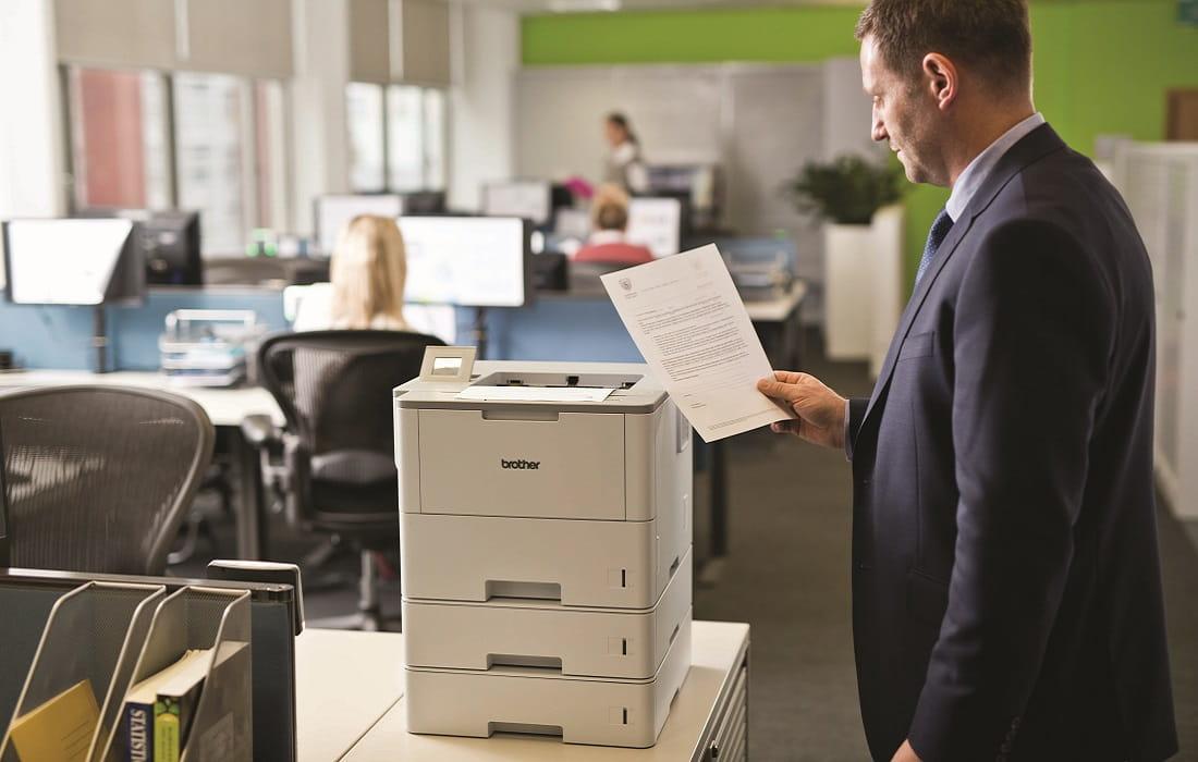 Impiegato in ufficio al lavoro con stampante laser monocromatica Brother HL-L6400DW