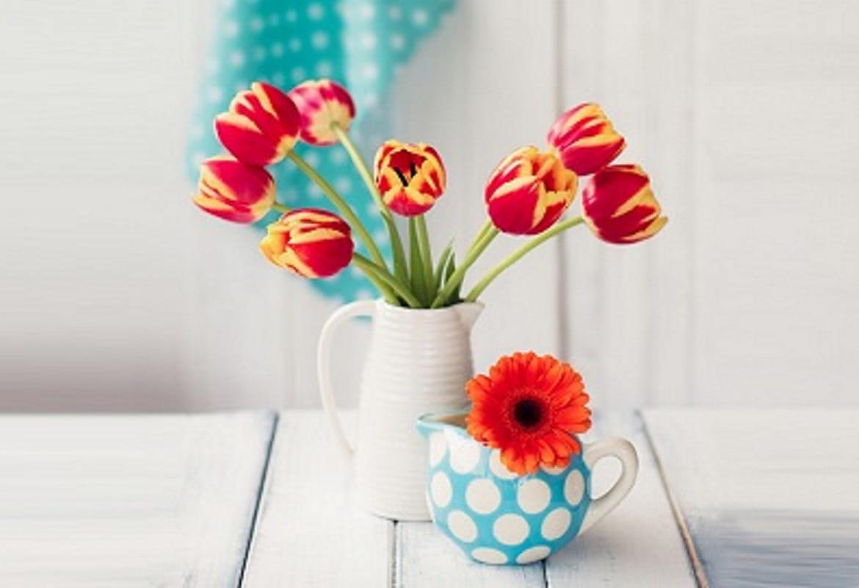 Vaso e tazza con fiori su scrivania