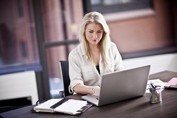 Impiegata alla sua scrivania al lavoro con pc portatile