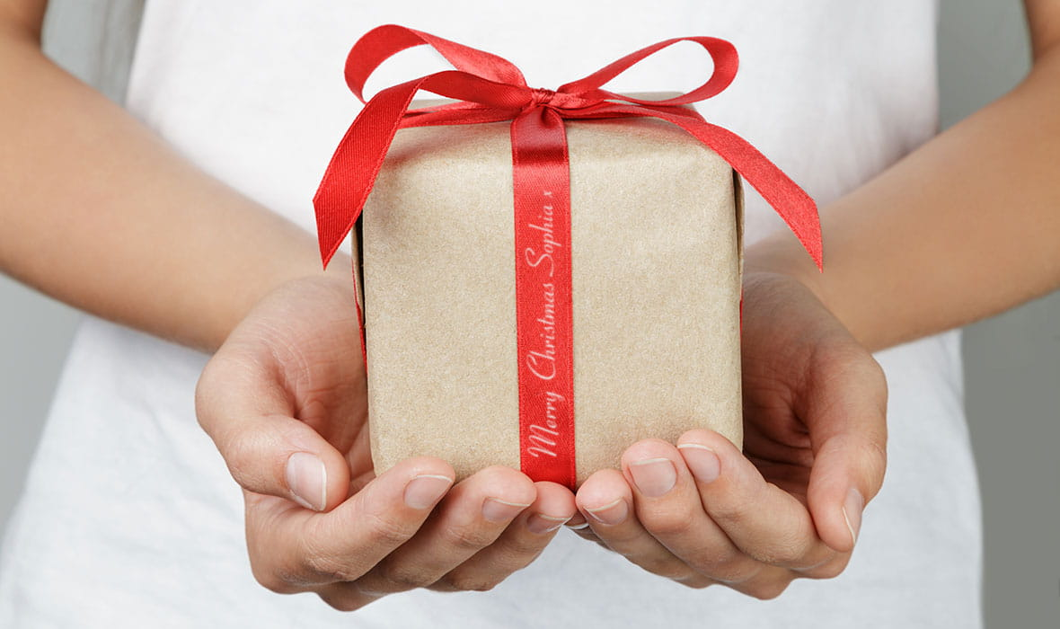 Donna con in mano un pacchetto regalo con messaggio personalizzato sul nastro rosso e scritta oro