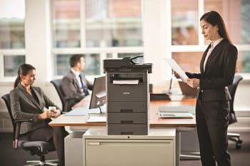 Stampante multifunzione laser monocromatica MFC-L5750DW all'interno di ufficio con impiegati al lavoro