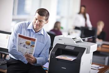 Impiegato in ufficio con stampa da stampante multifunzione Brother MFC-L8850CDW